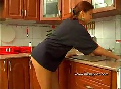 Sexy redhead teasing in the kitchen